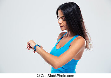 Fitness woman using fitness tracker on wrist over gray...