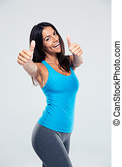 Smiling woman showing thumb up sign over gray background....