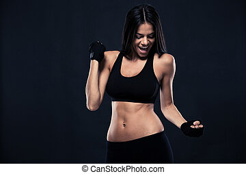 Happy fitness woman celebrating his success over black...