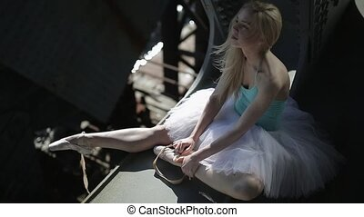 Blond dancer in a white tutu sits on the edge of bridge.