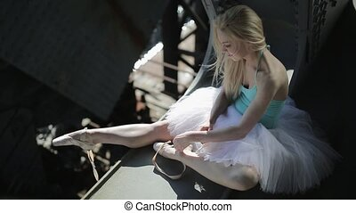 Blond dancer in a white tutu sits on the edge of bridge -...