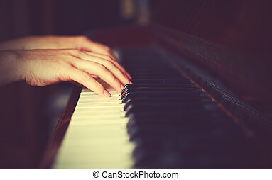 hands of woman pianist on piano keyboard - hands of a young...