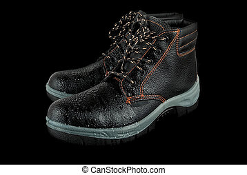 moist modern working boots isolated on a black background