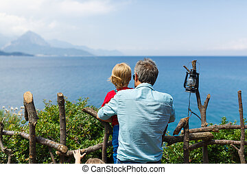 Father and son seeing on the blue sea