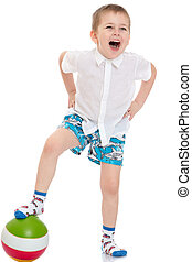 Funny little boy in shorts playing football