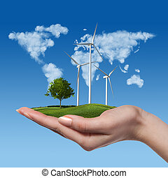 Wind turbines with tree in female hand - Wind turbines on...
