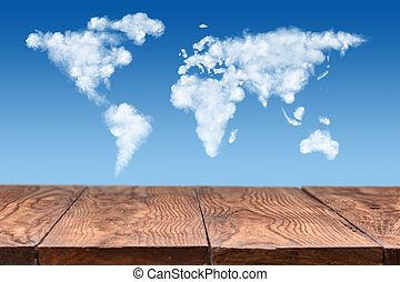 wooden table with world map made of clouds on sky