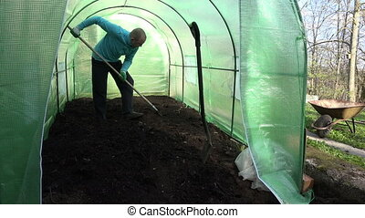 man work in greenhouse - gardener farmer work hard with soil...