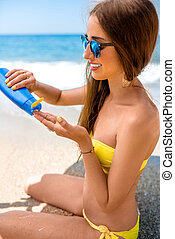 Woman using sun cream on the beach - Young woman in yellow...