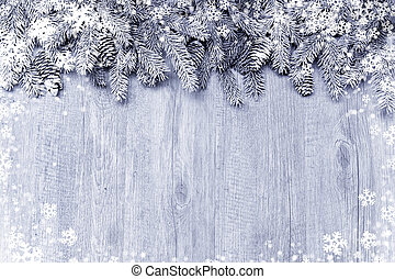 Snow-covered fir tree branch with decorations on wooden...