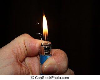 Ignitet lighter - flame - Ignitet lighter in a hand on black...