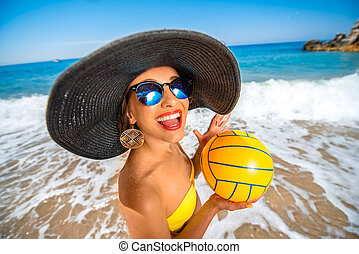 Woman with ball on the beach - Playful woman in big hat with...