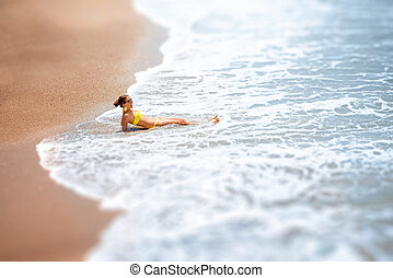 Woman lying on the sea coast - Young woman in yellow...