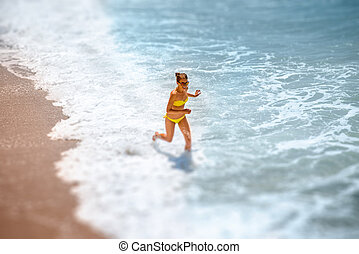 Woman running on the sea coast - Young woman in yellow...