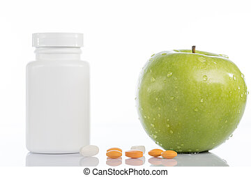 Natural green apple and various colored pills on white background