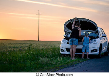 Mother and Son Repairing Something on their Car - Rear View...