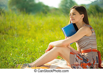 Beautiful young girl with book at wonderful green meadow -...