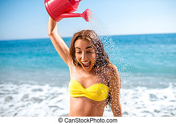 Woman pouring water from watering can on the beach