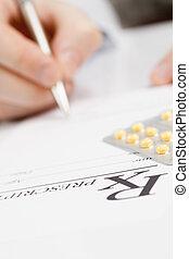 Doctor filling out drug prescription - studio shot