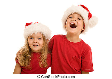Laughing christmas kids looking aside, wearing santa hats