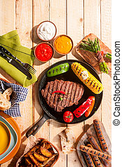 BBQ Grilled Meats and Vegetables on Picnic Table