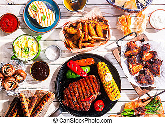 Barbequed Meats and Vegetables on Picnic Table - High Angle...