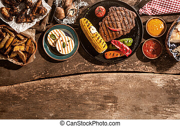 Grilled Meal Spread Out on Rustic Wooden Table - High Angle...