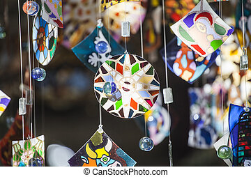 Colorful glass wind chime hanging outside, shallow focus