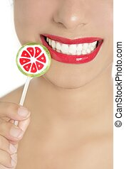Colorful Lollypop in perfect woman teeth