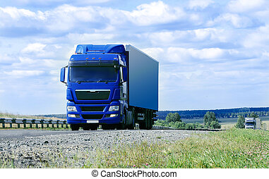 two big trucks move on highway in sunny summer day