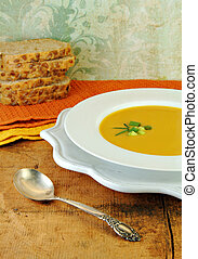 Squash Soup in White Bowl with Bread - Squash soup with...