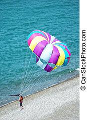 Multi coloured parachute over the blue sea