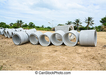 Concrete drainage pipes stacked for construction,...