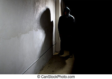 Stalker in a Dark Alley - hooded criminal stalking in the...