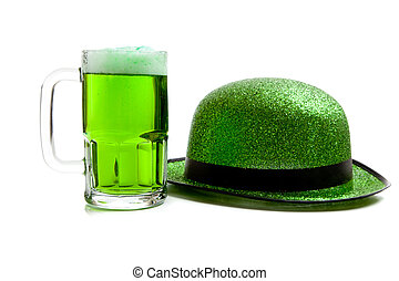 Mug of green beer and green glitter hat on white - A mug of...