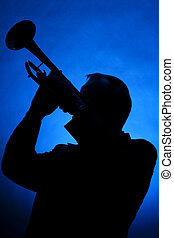 Trumpet Musician Silhouette on Blue - A silhouette of a...