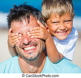Boy with dad playing at the beach - Little boy covers his...