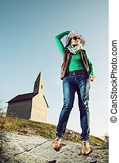 Young woman with stylish hat and an old romanesque church Archangel Michael