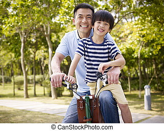 asian father and son enjoying biking outdoors - asian father...