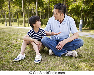 asian father and son having a conversation - asian father...