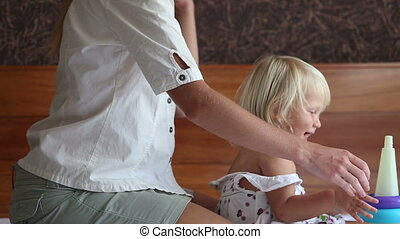 mother brushes small blonde daughters hair on sofa - mother...