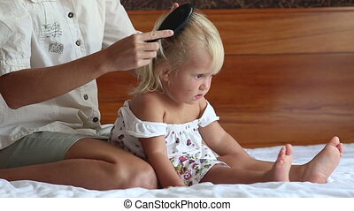 mother dresses hair-tail to small daughter on sofa - mother...