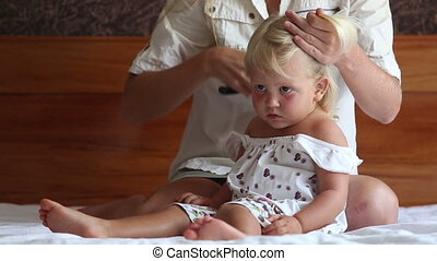 mother plaits hair to small daughter watching cartoon -...