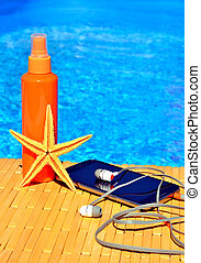 Cell phone, sun spray, head phones and starfish near water -...
