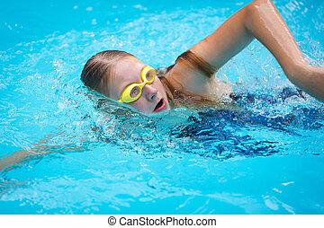 Young girl in goggles and cap swimming crawl stroke style