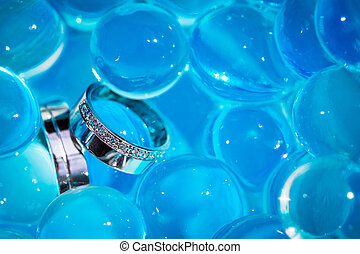 Wedding rings amid blue balls