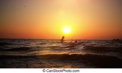 Silhouettes of young swimming couple playing in sea, floats...