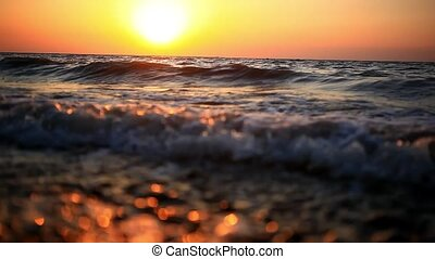 Bright sunset under the sea with waves splashes, fly spray...