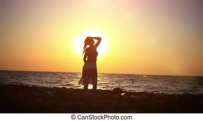 young romantic woman walking to the sea at amazing sunset beach