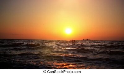 Silhouettes of young swimming couple hugging in love and kiss, floats ship at amazing sunset. Waves splashed against shore, reflections Of The sun is reflecting In beautiful water. Concept OF tourist holidays